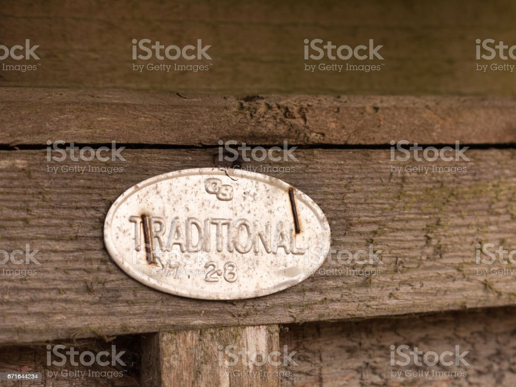 a metal sign stapled to a fence saying traditional oval shining retro vintage wooden background stock photo