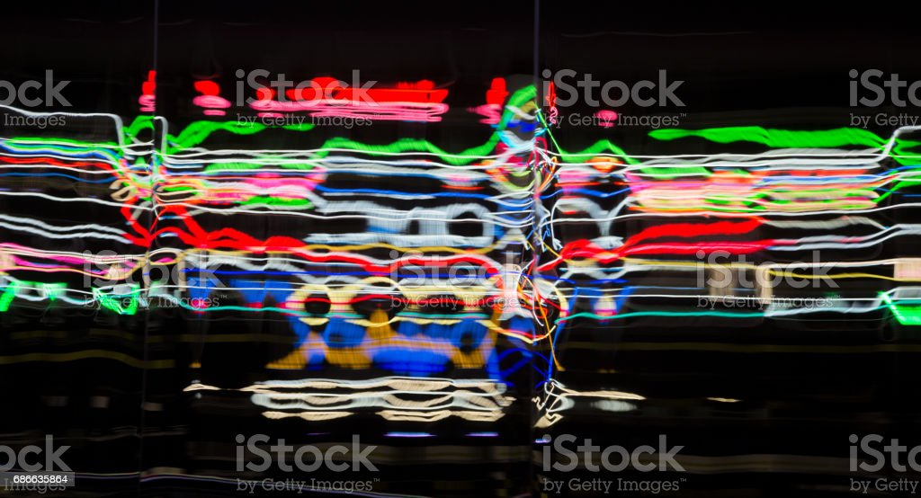 a metal wall is reflecting colorful neon lights stock photo