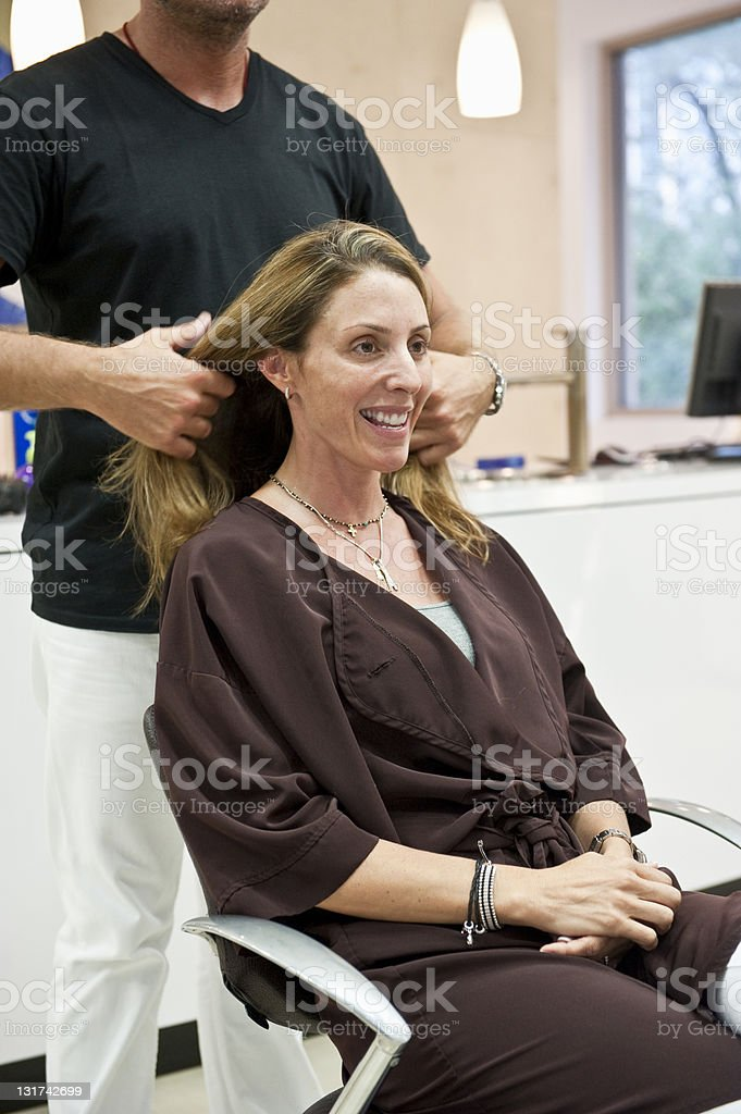 a middle aged woman getting her hair cut at salon royalty-free stock photo