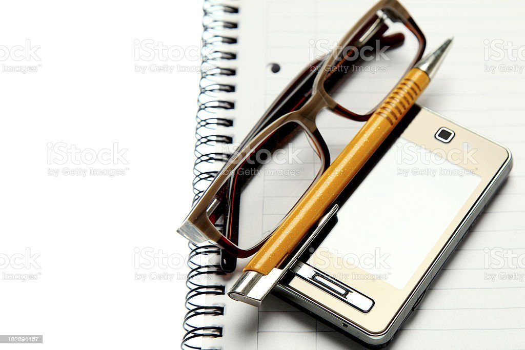 a pen, pair of glasses, and cell phone sitting on a notepad royalty-free stock photo
