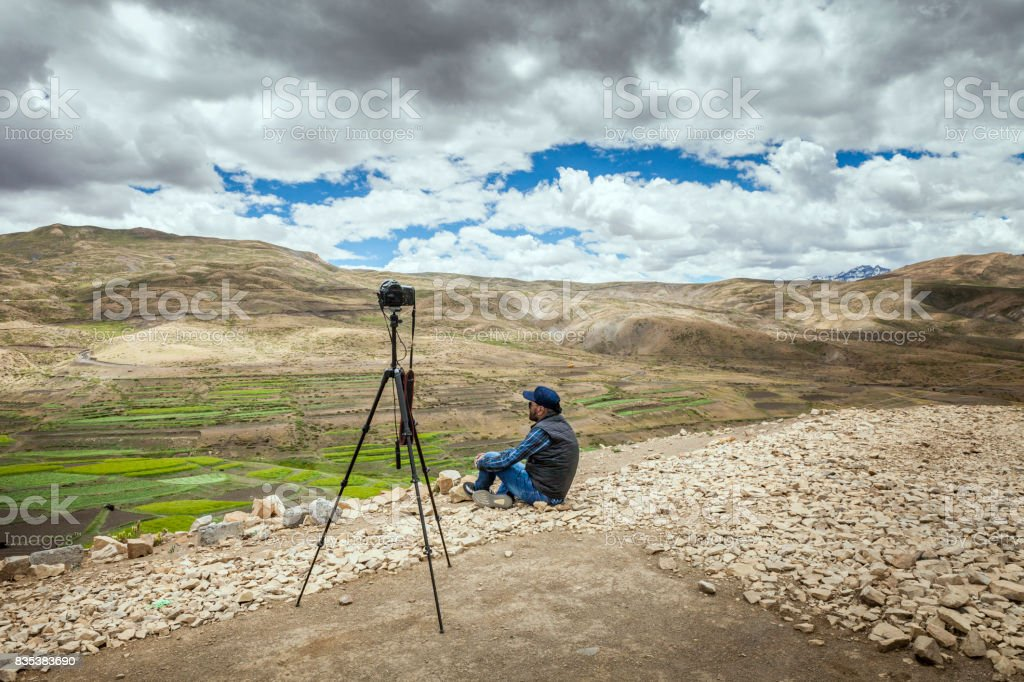 a photographer sitting on ground and taking pictures for timelapse stock photo