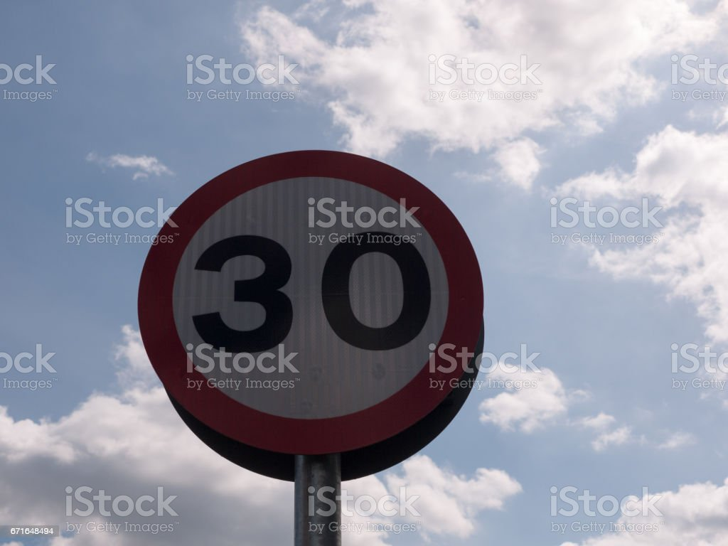a road traffic sign with a sky background saying 30 speed limit near school accident crash cars fast and slow warning stock photo