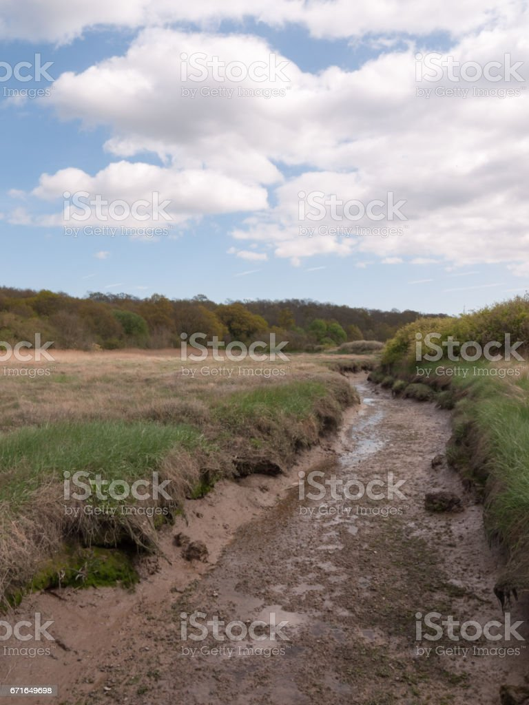 a shallow ditch of shining mud outside in a field in the country next to a running river, taken from a bridge in day time with white clouds overhead in the blue sky stock photo