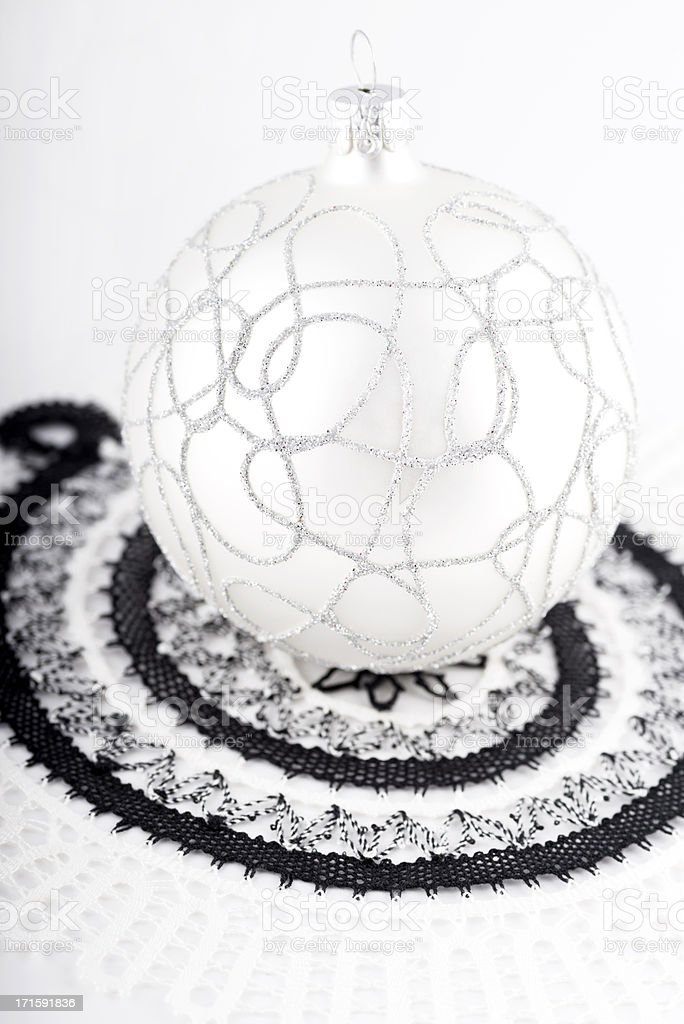 a shiny white bauble with black lace decoration around it royalty-free stock photo