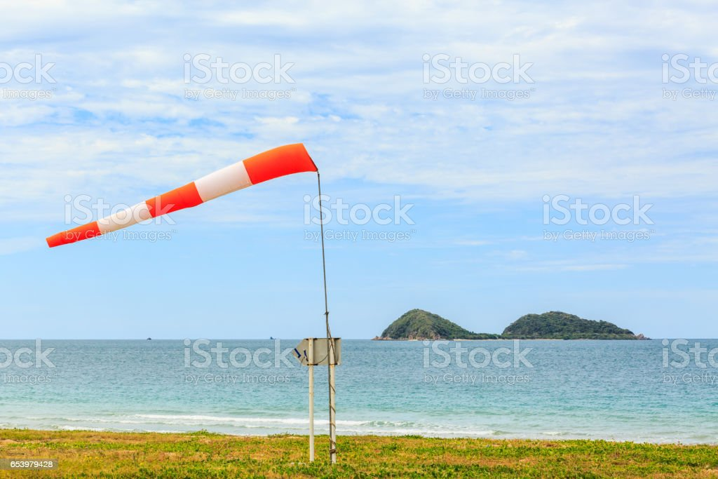 a wind force (windsock) against the dark sea and blue sky stock photo