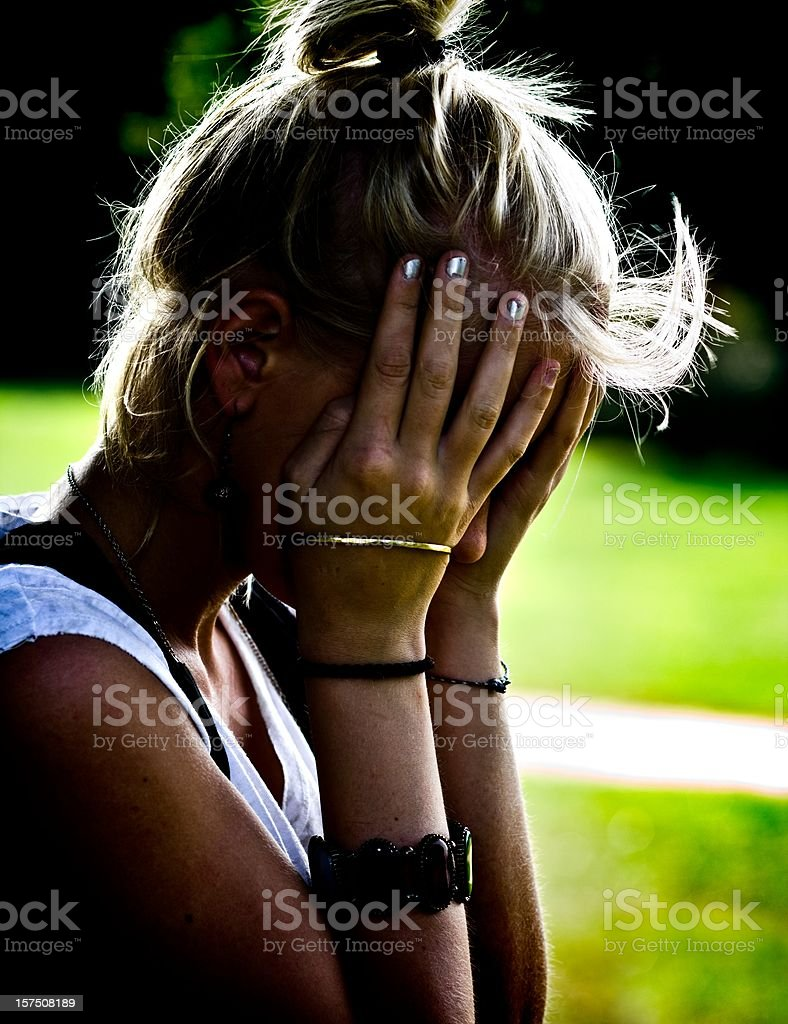 a young blonde female with her hands on her head looking upset royalty-free stock photo