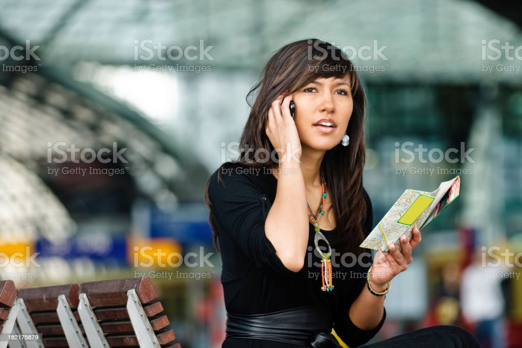 a young brunette woman on the cellphone holding a map royalty-free stock photo