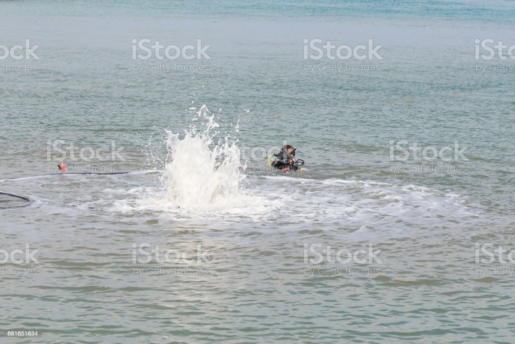 Aaqualung blowing sand in sea for pillars. stock photo