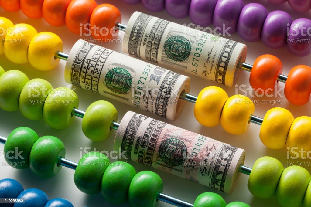 Abacus with rolls of dollar banknotes stock photo