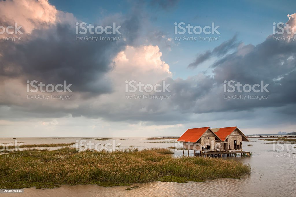 abadonded hut on dam with nice sky stock photo