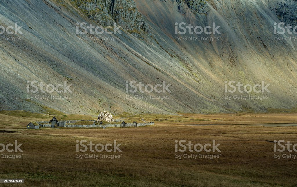 Abandon cottage in yellow field with mountain range Vesturhorn Iceland stock photo