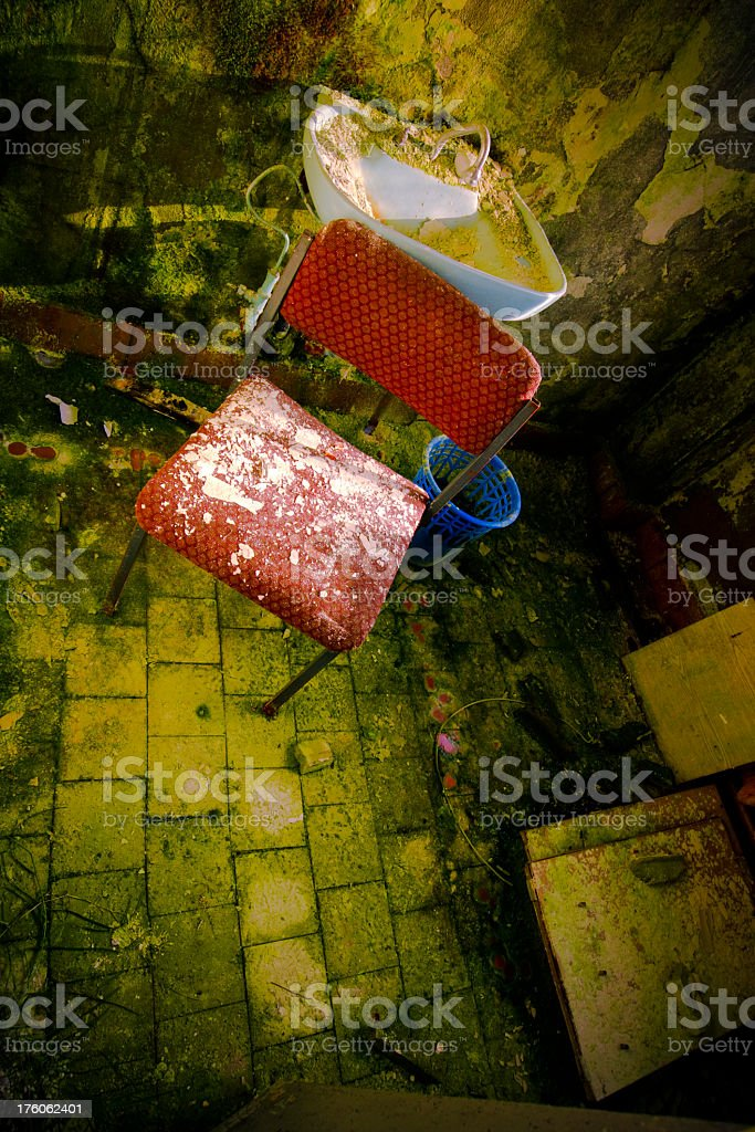 Abandonded bathroom with chair, sink and basket royalty-free stock photo