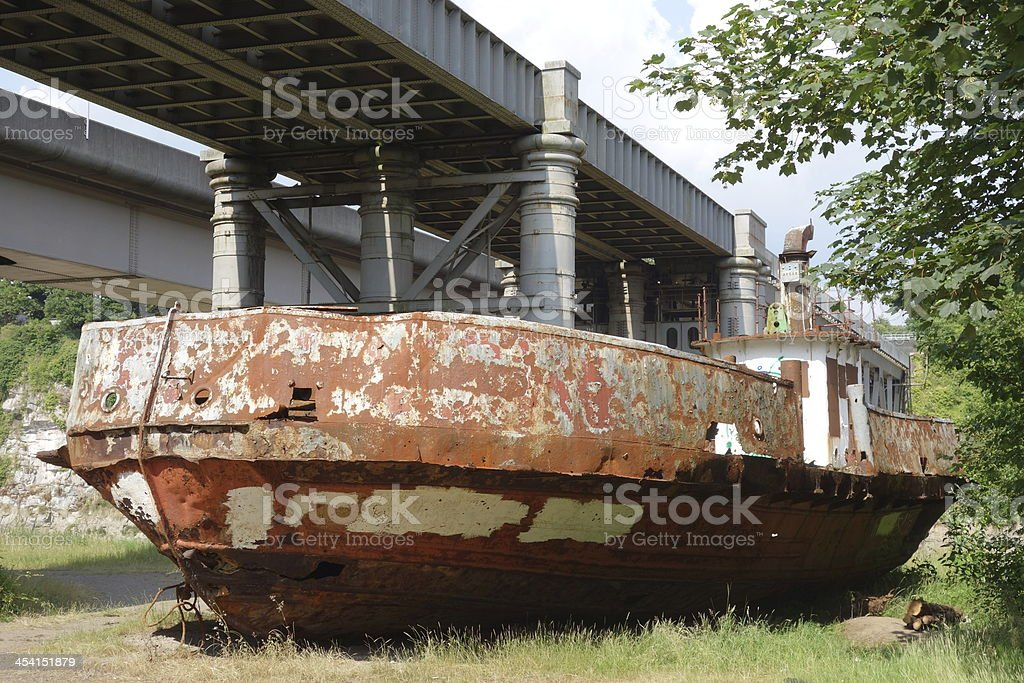 abandoned and beached car ferry left to rot under bridge royalty-free stock photo