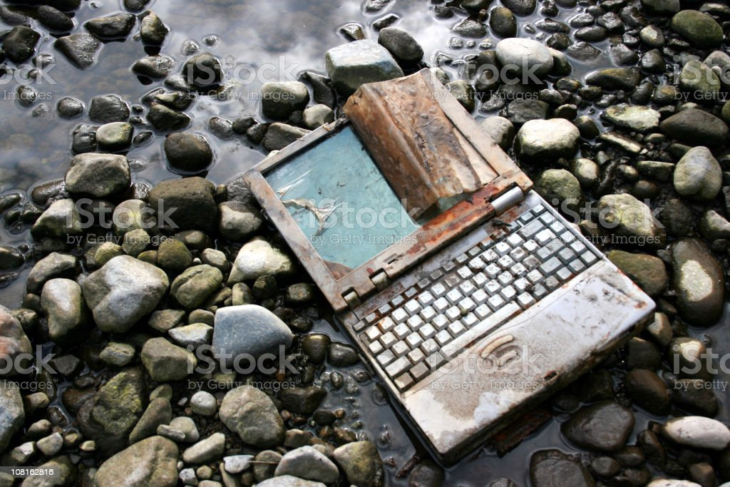 Abandoned and Rusted Laptop Lying on Riverbed stock photo