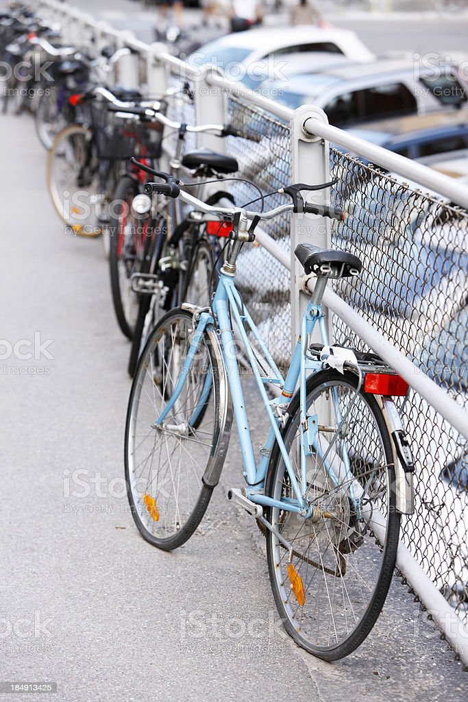 Abandoned bicycle on street leaning against fence royalty-free stock photo