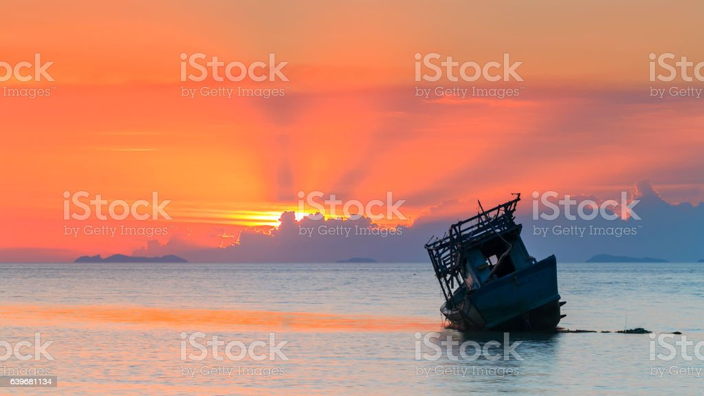 abandoned boat at the sea in sunset Time stock photo