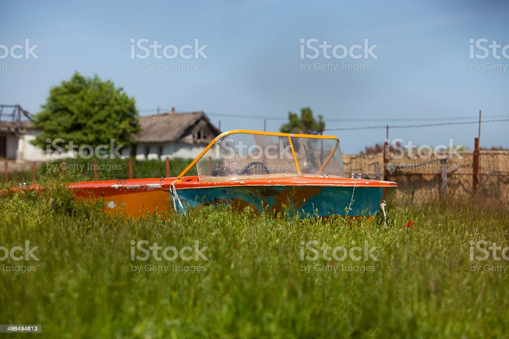 Abandoned boat in green field stock photo