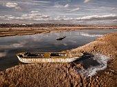 Abandoned broken ship in autumn river.