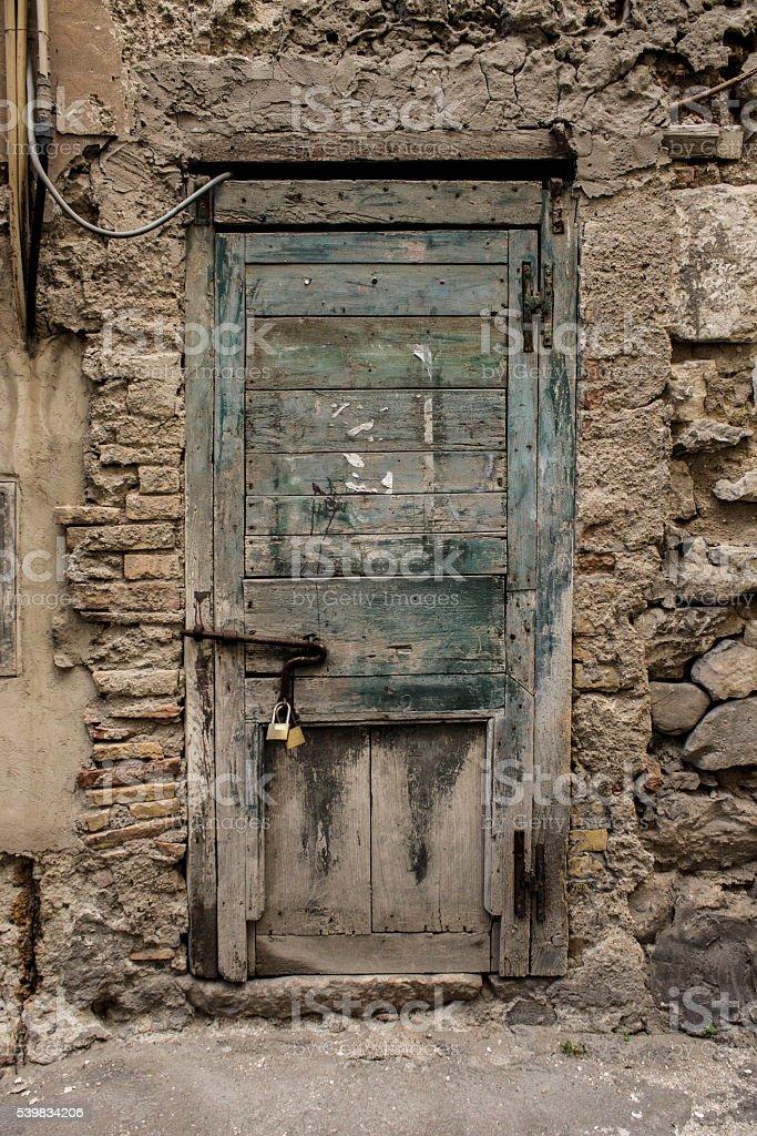 Abandoned building. Scraped locked door. Stone's wall stock photo