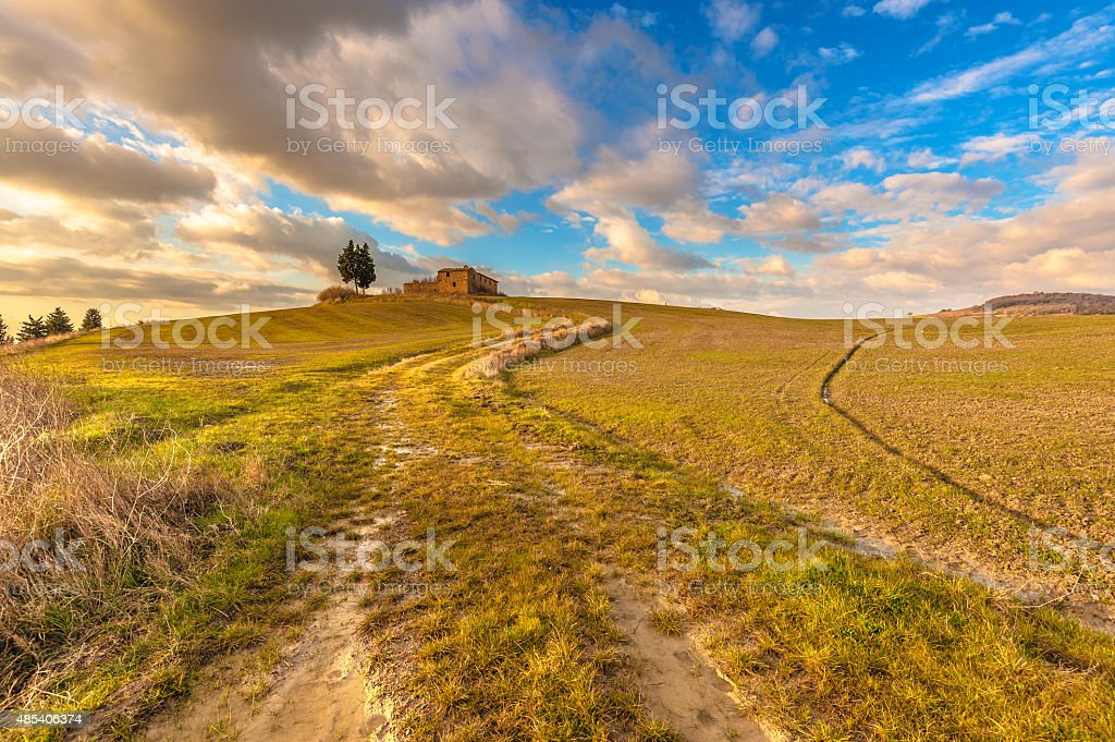 Abandoned buildings between the Tuscan fields with blue cloudy s stock photo