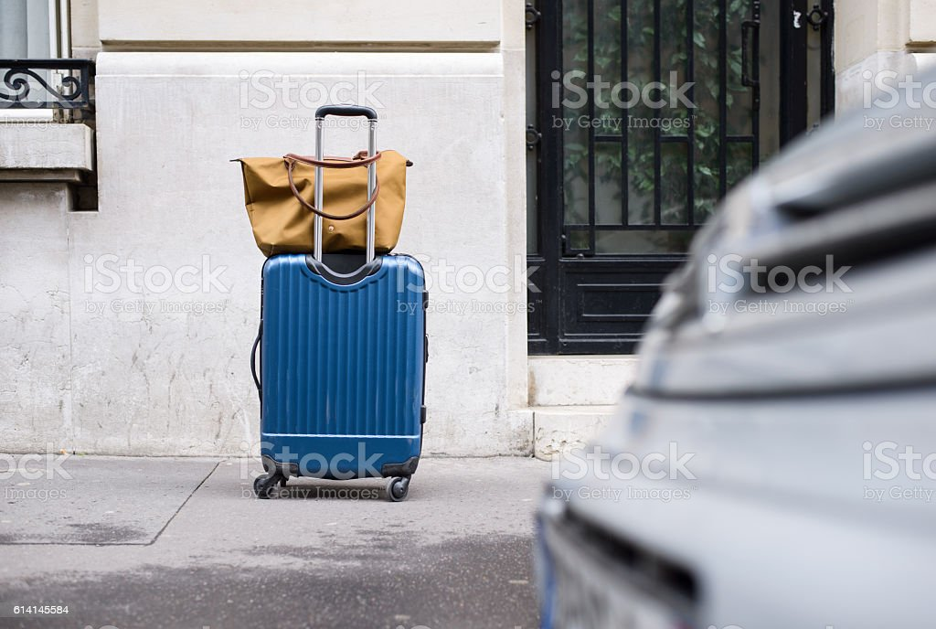 Abandoned Case with Wheels on City Pavement stock photo