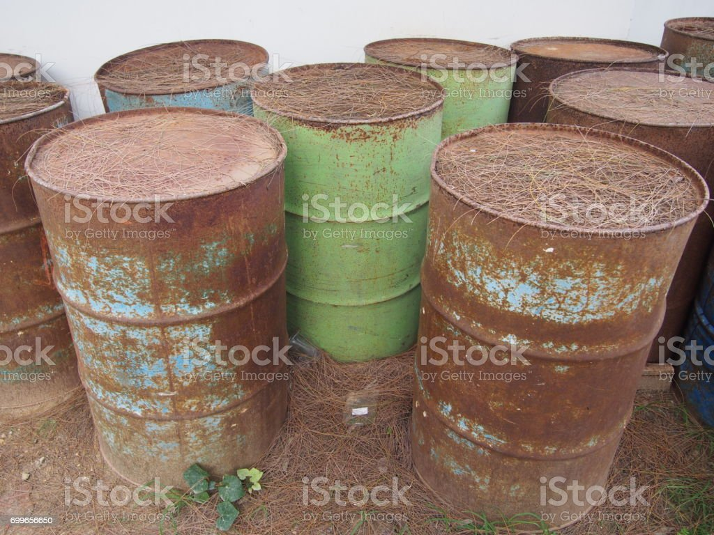 abandoned corroding rusty oil barrels on the ground stock photo