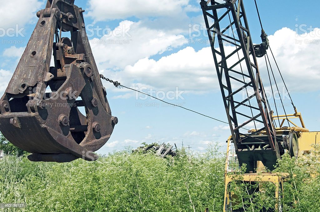 Abandoned crane in weed patch stock photo