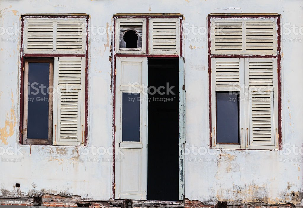 Abandoned Facade White Building showing ruined Wooden Door and windows royalty-free stock photo