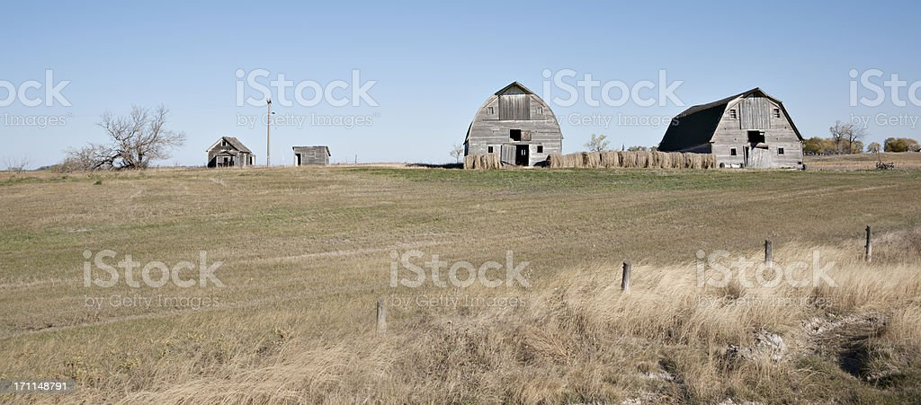 abandoned farmstead with weathered gray buildings royalty-free stock photo