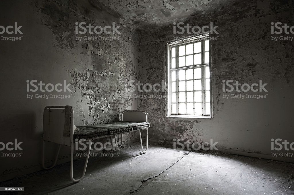 Abandoned hospital with a bed in the corner royalty-free stock photo