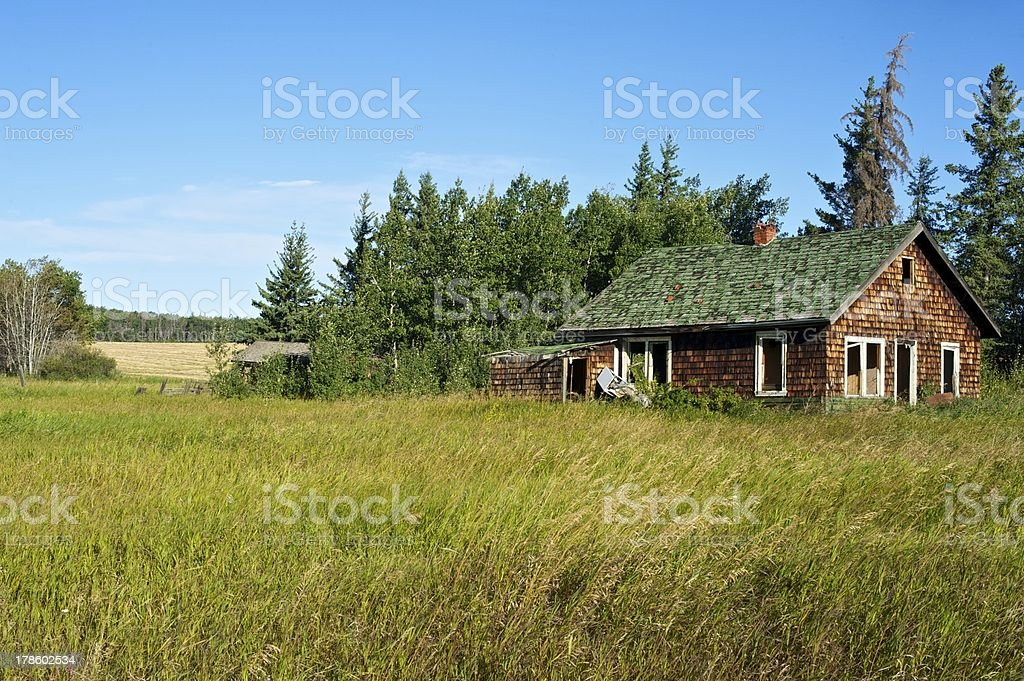 abandoned house in grassy field royalty-free stock photo