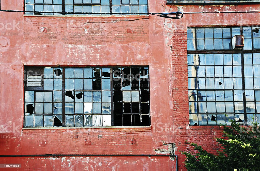 Abandoned industrial red brick building with broken windows stock photo
