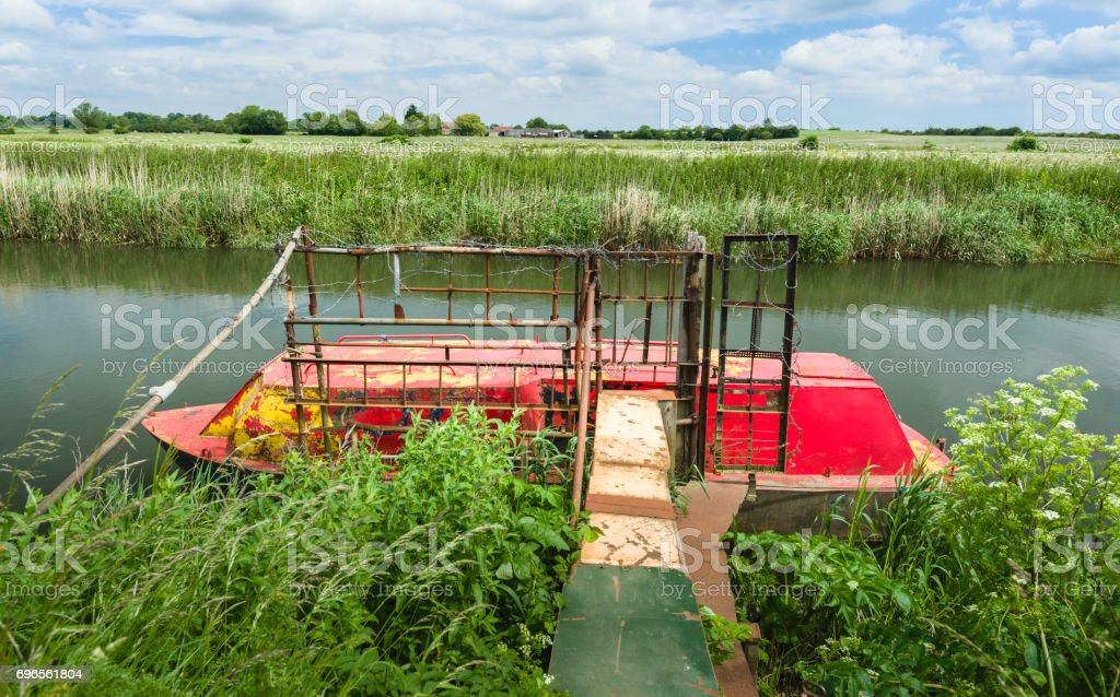 Abandoned ironclad river boat on the river Hull flanked by overgrown vegetation. stock photo