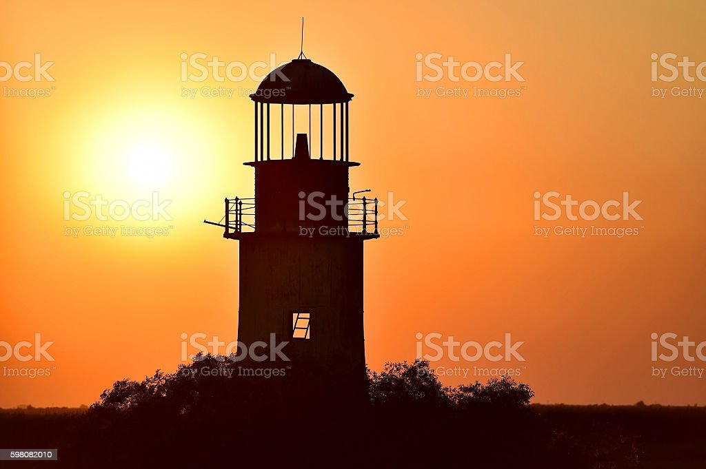 Abandoned lighthouse at sunset on a river stock photo