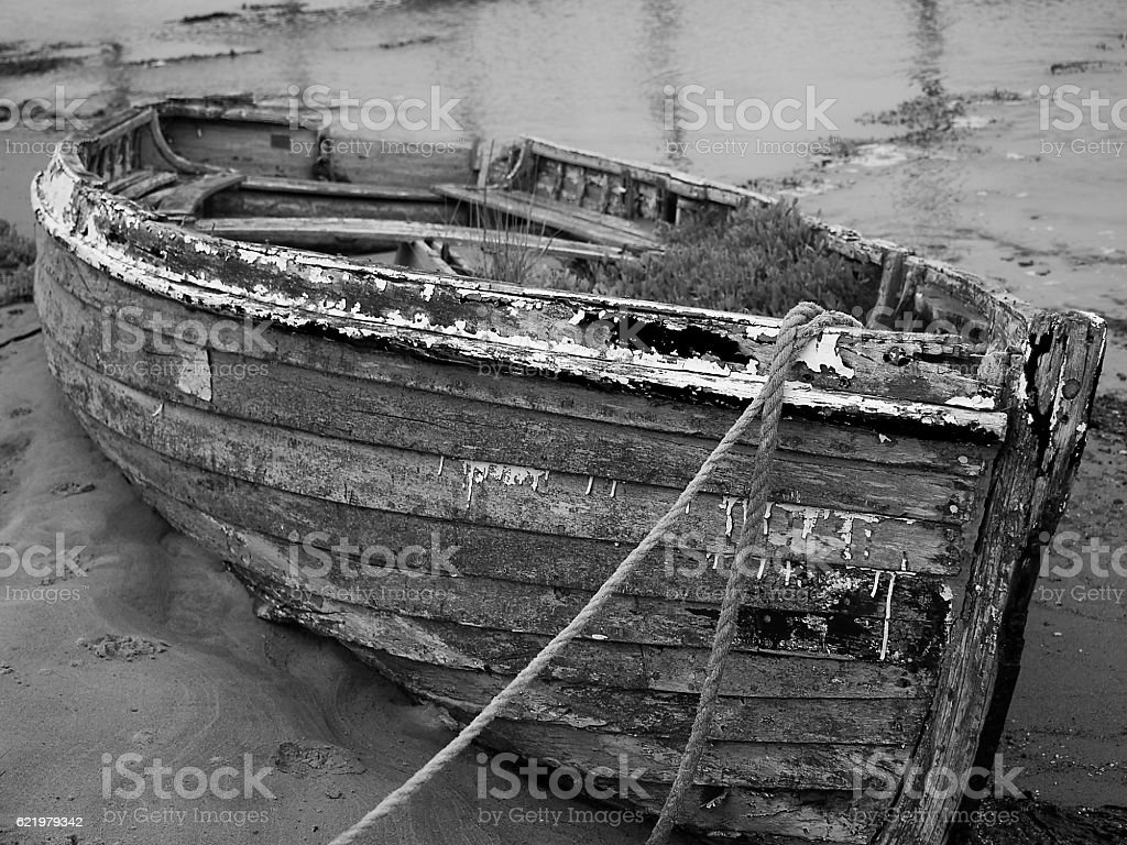 Abandoned old boat decaying on mud flats stock photo