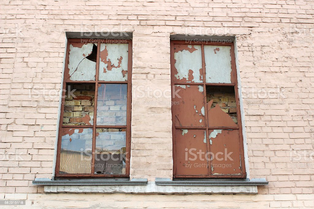 Abandoned place, broken windows of old damaged building stock photo