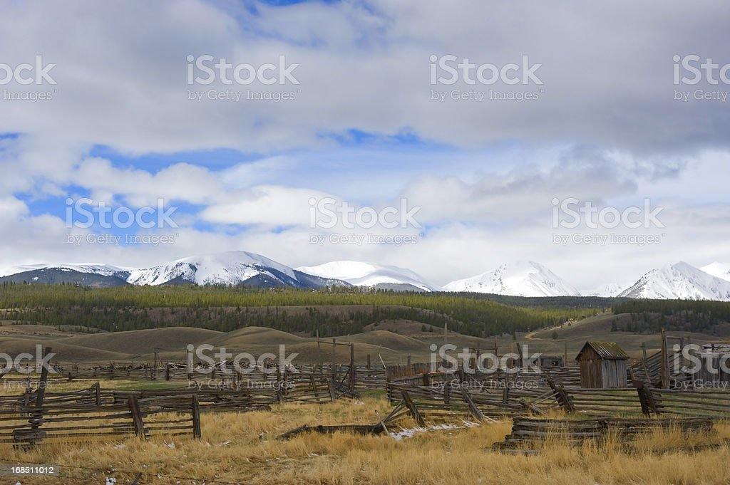 Abandoned Ranch Against Snow Covered Mountain Backdrop stock photo