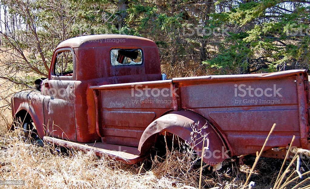 Abandoned red and  rusty 1950's farm pickup truck stock photo