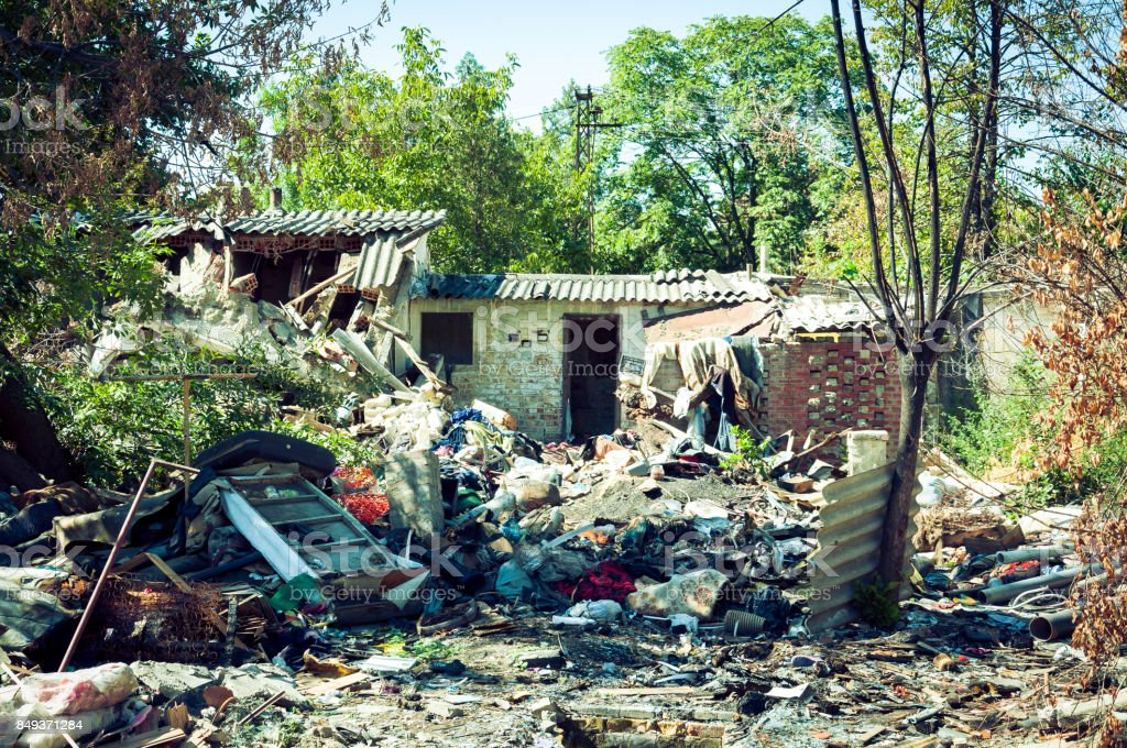 Abandoned ruin of house after grenade explosion in bombing with remains all over the yard stock photo