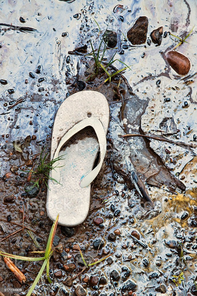 Abandoned Sandal on A Toxic Beach stock photo