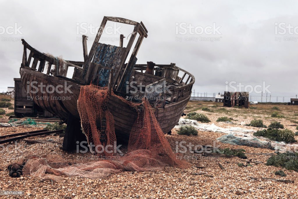 abandoned ship on pebble beach stock photo