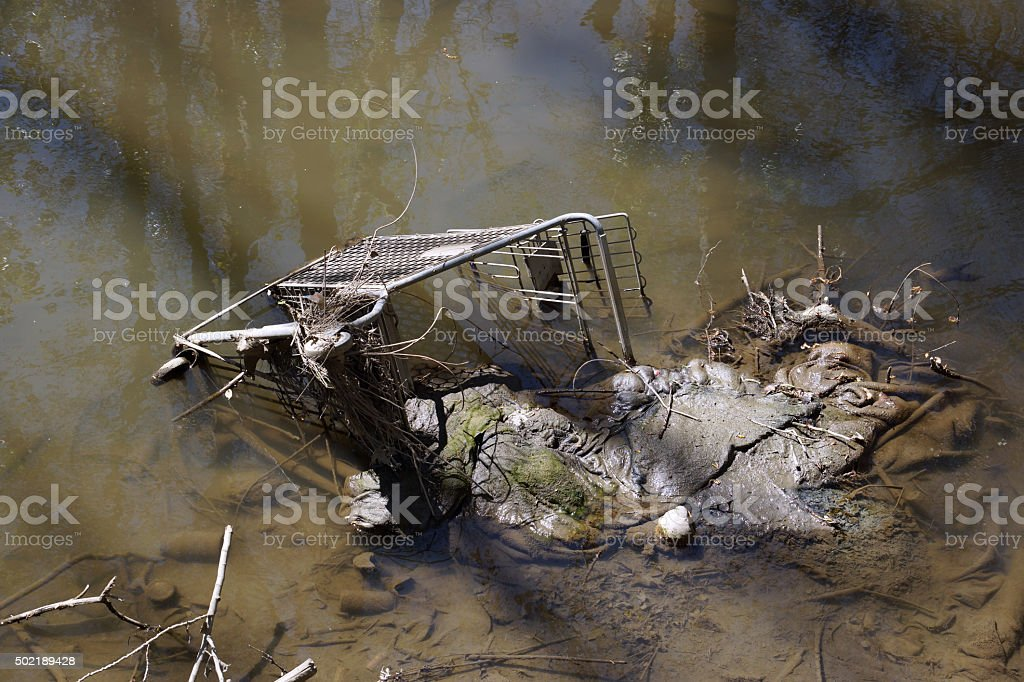 Abandoned shopping trolley in muddy water stock photo