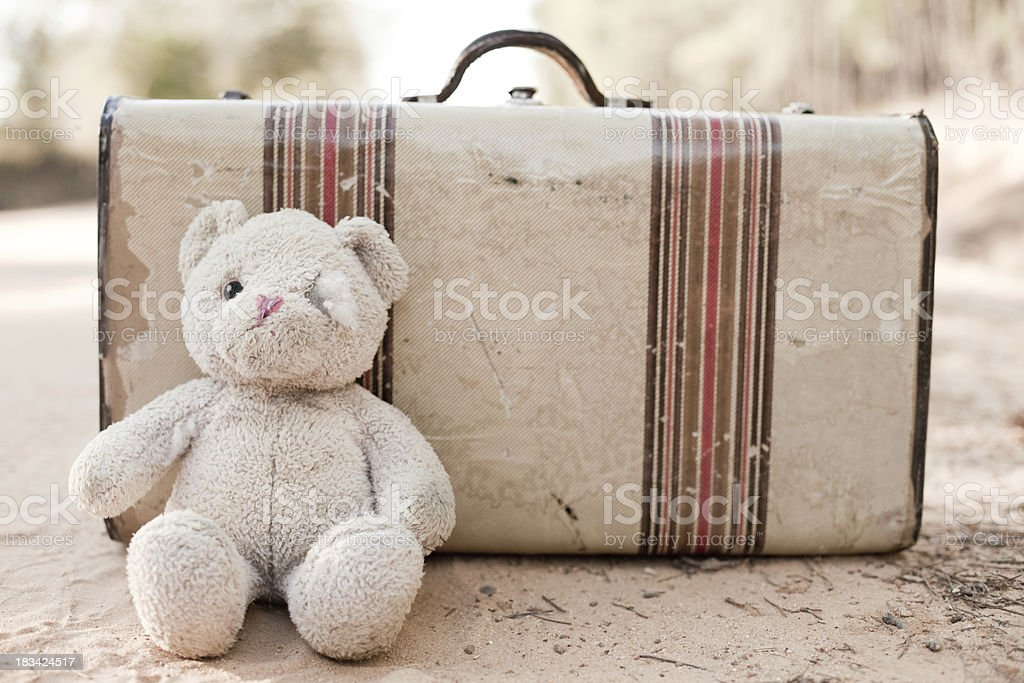 Abandoned Suitcase with Teddy Bear on Dirt Road royalty-free stock photo