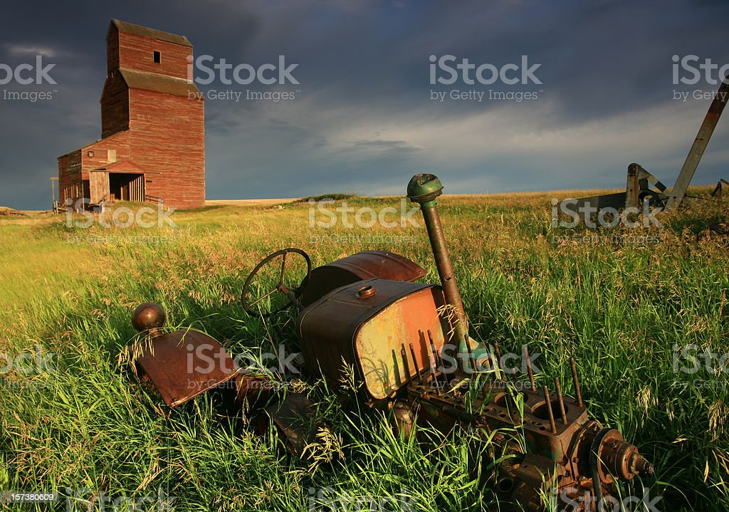 Abandoned Tractor and Grain Elevator on the Great Plains royalty-free stock photo