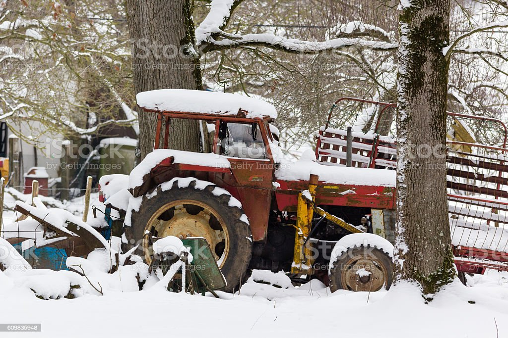 abandoned tractor in the snow stock photo