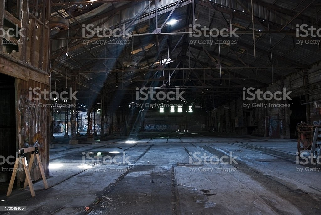 Abandoned warehouse with sun peeking through roof stock photo