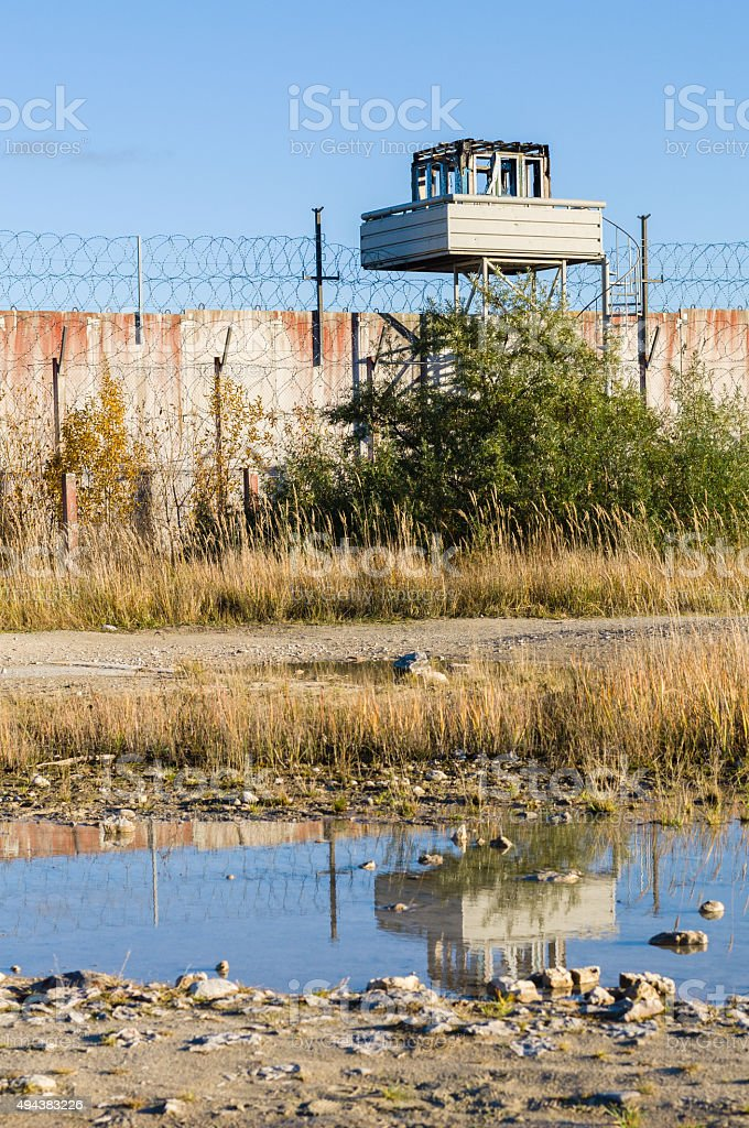 Abandoned watch-tower and prison wall with reflection in puddle stock photo