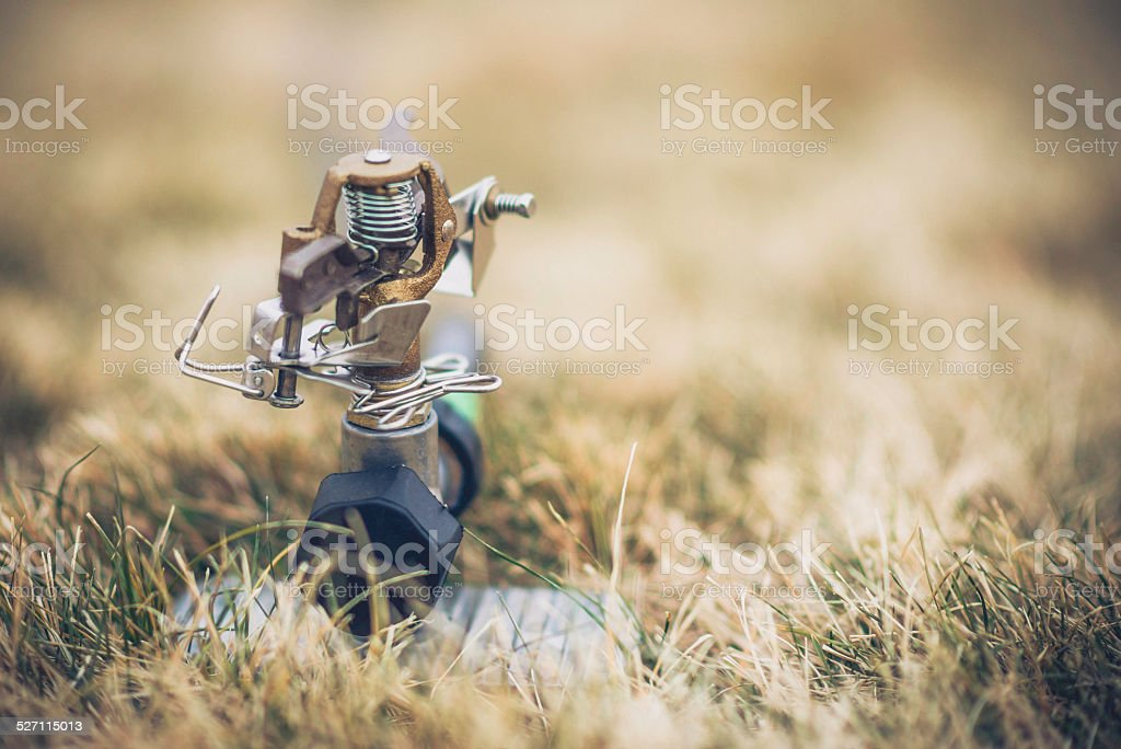 Abandoned water sprinkler in dry dead grass stock photo