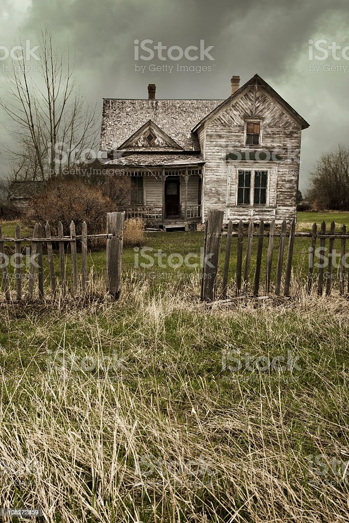 Abandoned white farmhouse in field with brown wooden fence stock photo