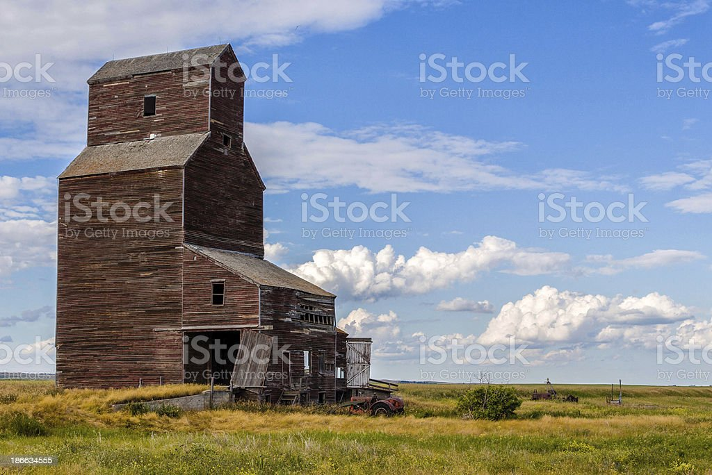 abandoned wood grain elevator under blue cloud filled sky royalty-free stock photo